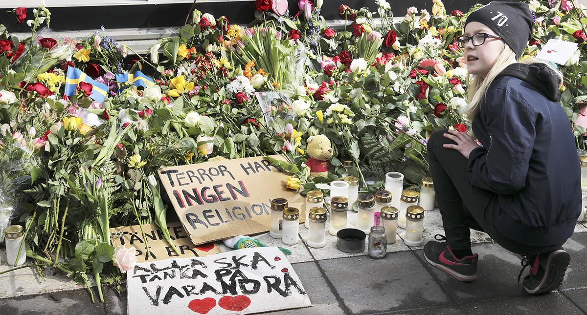 Flicka vid blomsterhav efter terrorattacken på Drottninggatan