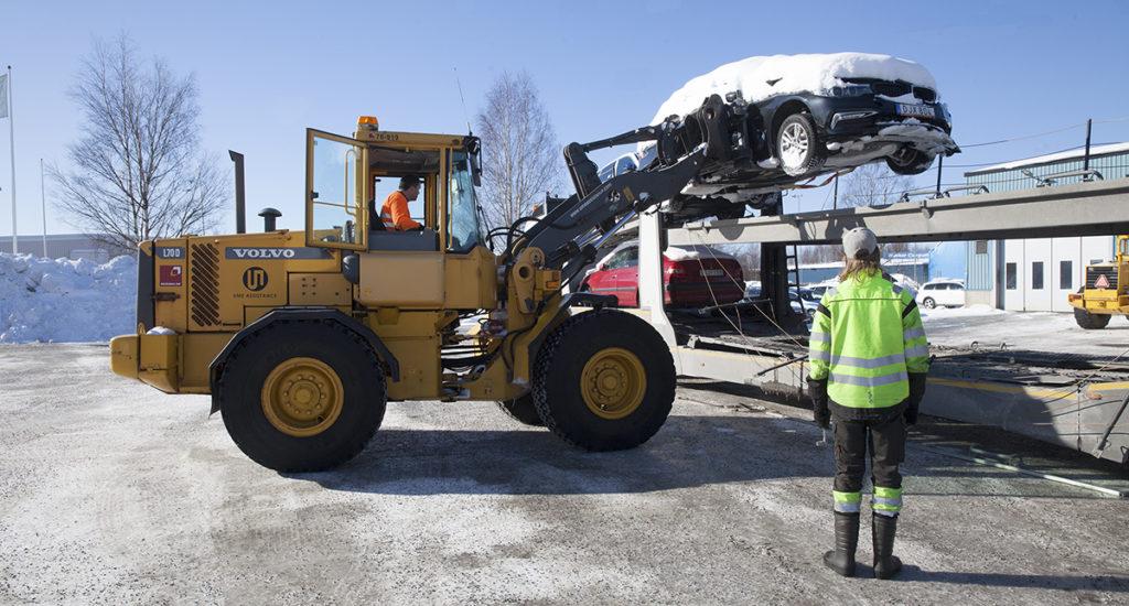 Ume Assistance. Jörgen Björk tar hjullastaren och lyfter upp kraschade bilar på en biltransporttrailer som ska flytta dem till skroten.