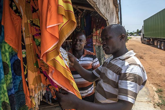 Clever och Prosper hinner med lite shopping under den flera timmar långa väntetiden vid gränsen mellan Uganda och Rwanda.