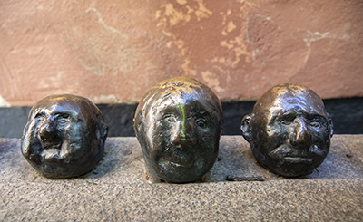 På Gåstorget i Gamla stan i Stockholm blickar tre manshuvuden upp på skulptören Sven Lundqvists Tungviktare, som går en rond i en staty.