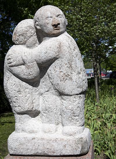 Beskyddande och omhändertagande. Är det dagens mansroll? I Larsbergs centrum på Lidingö håller en man om sin kvinna i bildhuggaren Sven Lundqvists Tröst.
